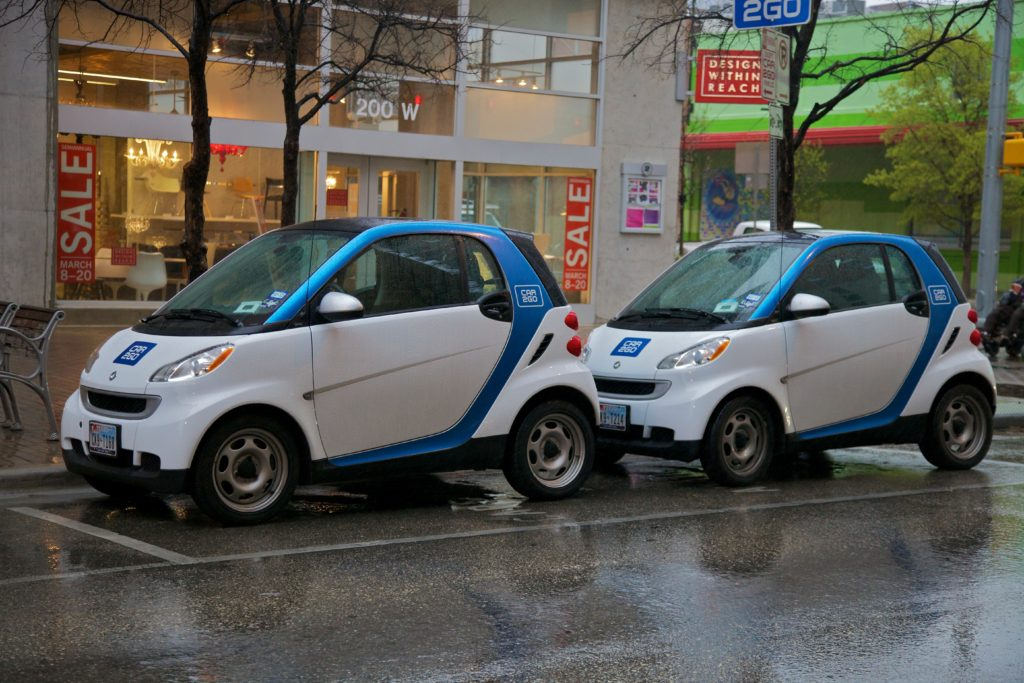 Two Car2Go cars parked on the street.