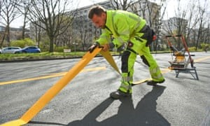 City worker lays tape in Berlin for temporary bike lane during COVID