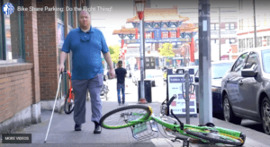 Photo of visually impaired man walking on the sidewalk with bikeshare bike improperly parked