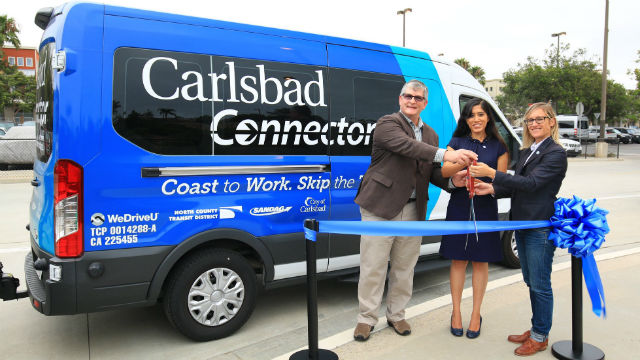Ribbon cutting with Carlsbad Connector-branded shuttle van