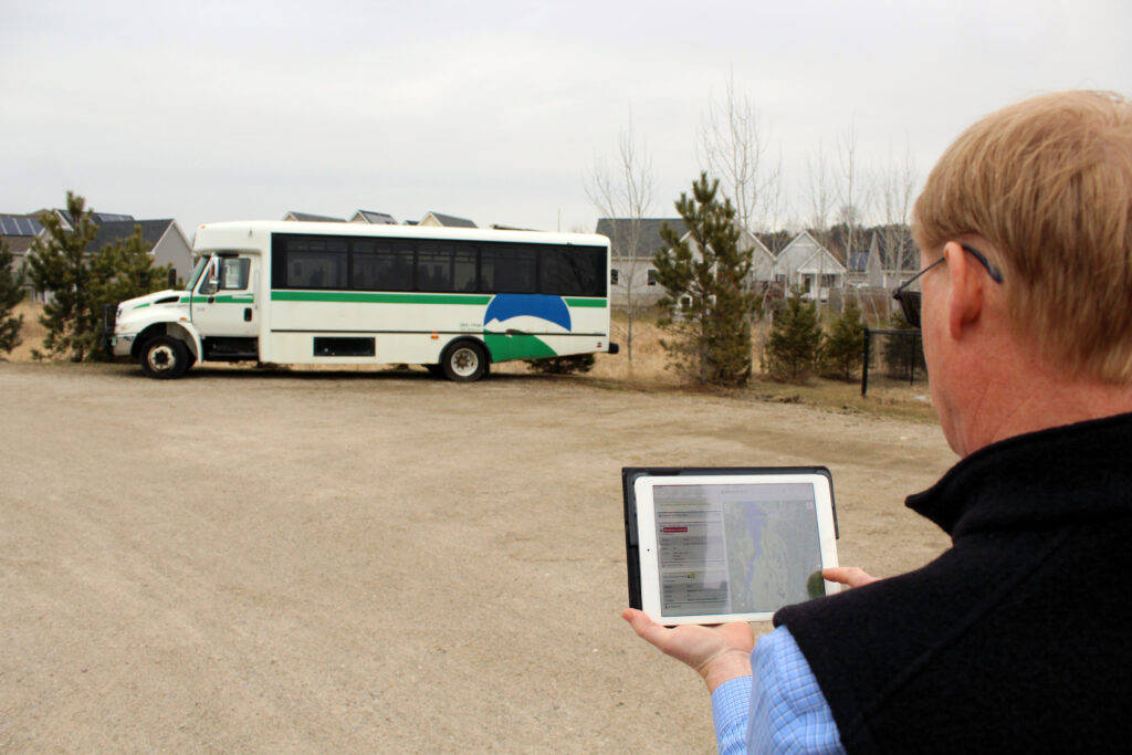 Man holds tablet displaying Go! Vermont Trip Planner in front of bus
