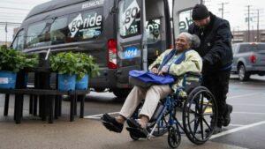 Woman in wheelchair departing GoRide bus, wheelchair accessible NEMT service