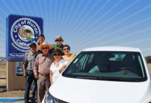 Green Raiteros group around electric car