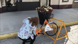 Pocahontas staff member crouches in front of Koloni bike in rack