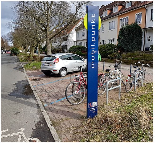 A picture of a mobility point in Bremen, Germany. It includes the sign, cycling parking and car sharing spots.