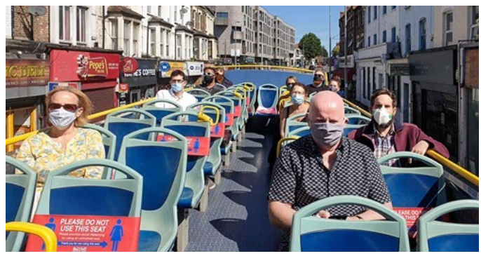 The second level of an open air bus in London with several riders wearing masks during COVID-19.