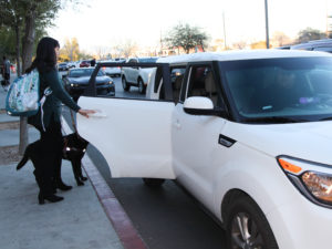 A visually impaired person entering a vehicle