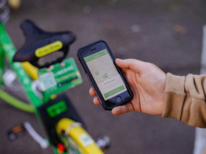 Photo of the bikeshare app and dockless bikeshare bicycle