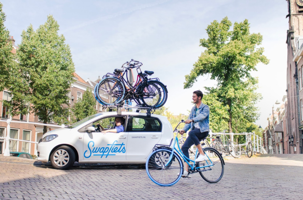 A man on a Swapfiets bike next to a Swapfiets repair car with a bike rack full of bikes on top of the car
