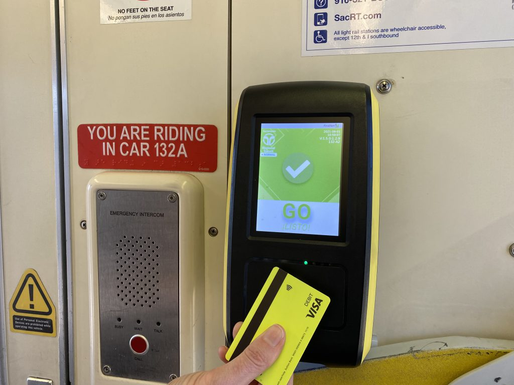 Image of passenger tapping contactless debit card to payment receptor on SacRT Light Rail