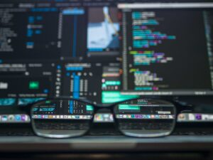 Stock photo of glasses on laptop with data processing programs on screen