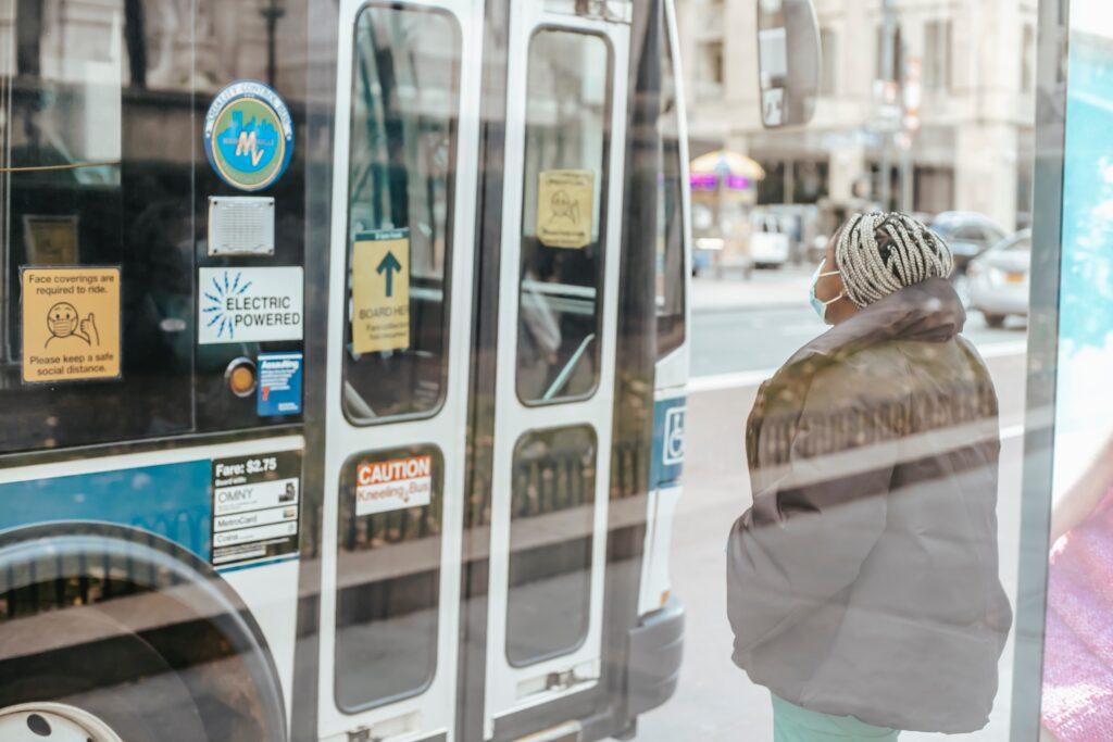 Woman wearing mask waits at bus stop