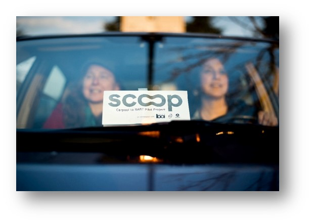 Photo of two people carpooling and the Scoop parking pass shown on the dashboard.