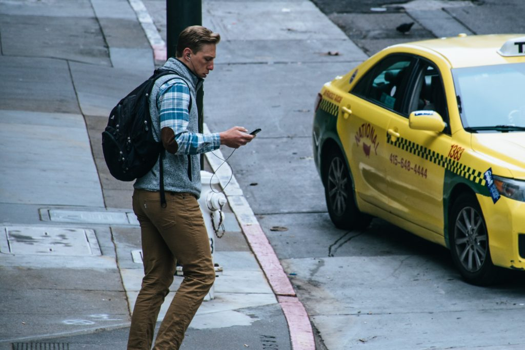 Man holding his phone on the curb and a taxi in the background.