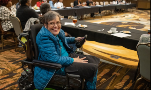 A picture of a planning meeting with a woman in a wheelchair able to participate.
